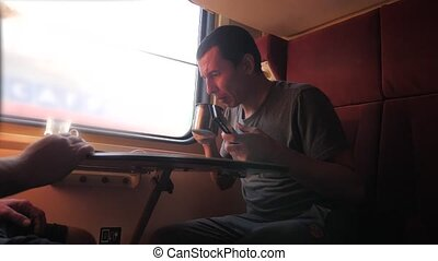 man is sitting on the train carriage holding a smartphone...