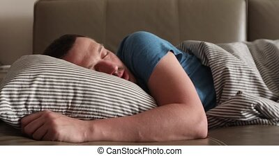 Man is sleeping on a couch - A man sleeps at home on a couch