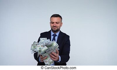 Man is smelling, throws and enjoys the falling dollar bills
