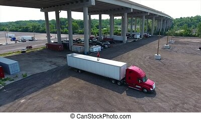 Man is standing on the truck. View from drone. Camera is moving around him.