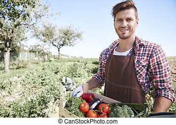 Man is standing with crate full of vegetables