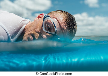 man is tired and lie on surfboard in the ocean