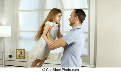Man is turning his daughter in a room - Man turns his...