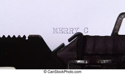 Man is typing a letter on the typewriter of a merry christmas. Close up