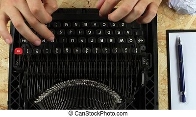 Man is typing on a printed retro typewriter. View from above