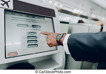Man is using ATM machine at airport