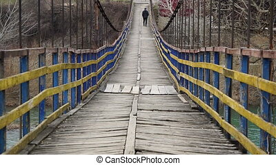 Man is walking along on a rope suspension bridge