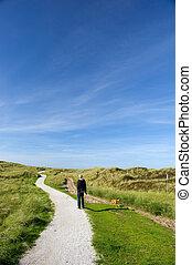 Man is walking in coast landscape