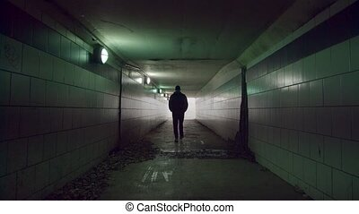 Man is walking to the end of the tunnel. Light at the end of the tunnel.