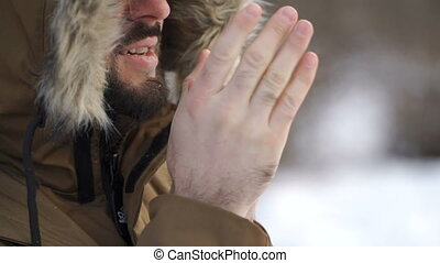 Man is warming his cold hands