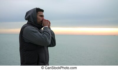 Man is warming up his hands by breathing at the cold morning...