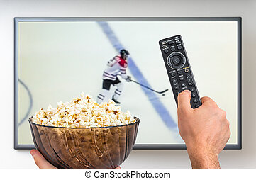 Man is watching hockey match on TV and holding tv remote...