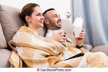 Man is watching TV with wife in time resting on sofa