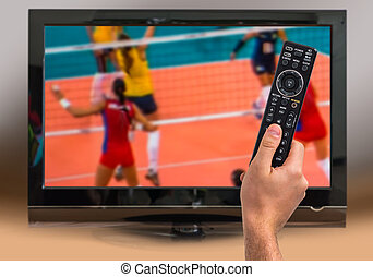 Man is watching volleyball match on TV