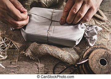 man is wrapping a gift, eco-friendly packaging with reusable and natural materials