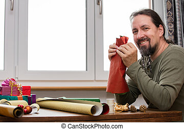 man is wrapping colorful gifts
