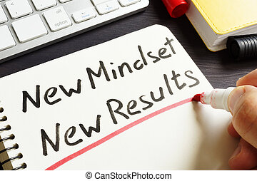 Man is writing New Mindset New Results.