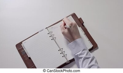 Man is writing notes in notebook. Part 06.