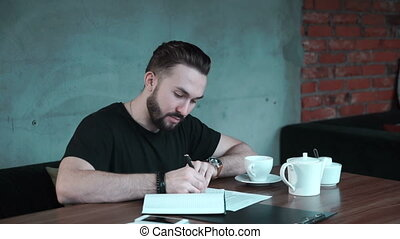 Man is writing something in copybook - Man is writing some...