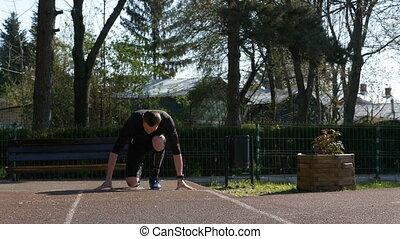Man jogger athlete in sportswear starting running from block...
