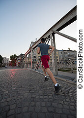man jogging across the bridge at sunny morning