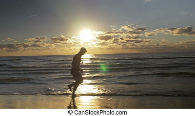 Man jogging barefoot on the beach at sunrise