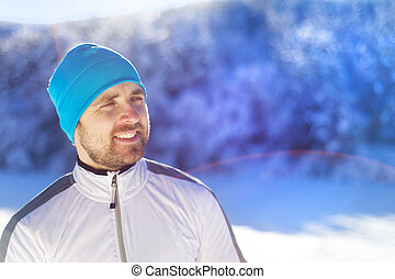 Man jogging in winter nature - Young runner warms him up...