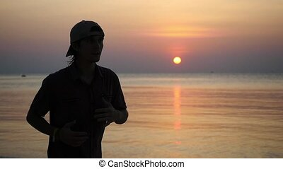 Man jogging on beach during sunset, slow motion. - Man...