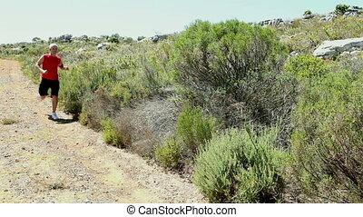 Man jogging through a wild terrain