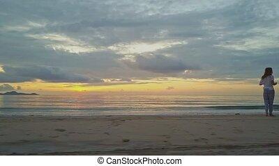Man Jogs on Beach against Golden Sunrise above Sea