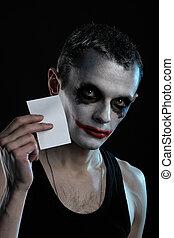 Spooky man joker on black background