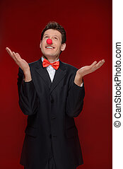Man juggling. Cheerful man with a clown nose juggling while standing isolated on red