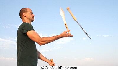 Man Juggling Knives - Man throwing three knives in the air...