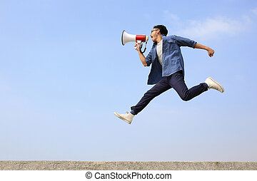 man jump and shout by megaphone with blue sky background, asian
