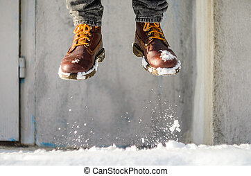 Man jump on a snowy street. Brown leather shoes in the snow. Takeoff concept