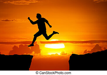 Man jump through the gap between the cliff
