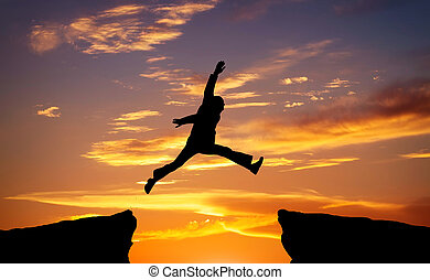 Man jump through the gap on sunset fiery background. Element of