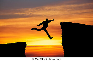 Man jumping across the gap from one rock to cling to the...