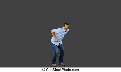 Man jumping and gesturing on grey screen