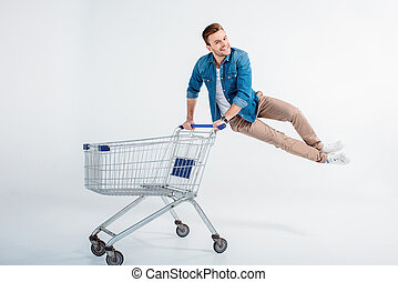 man jumping and having fun with shopping trolley on white