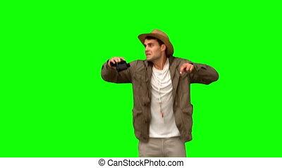 Man jumping and using binoculars on green screen in slow...