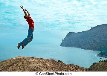 Man jumping cliff