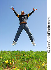 Happy man jumping on green grass
