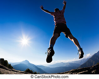 Man jumping in the sunshine against blue sky. Concept:...