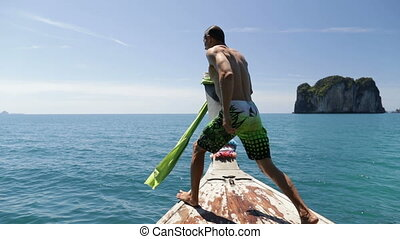 Man Jumping In Water From Long Tail Boat Nose Back Rear...