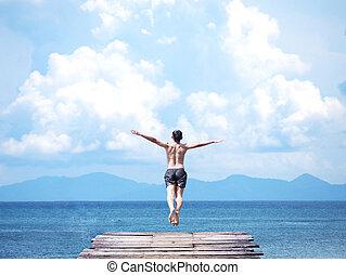 man jumping off wooden bridge into blue sea.