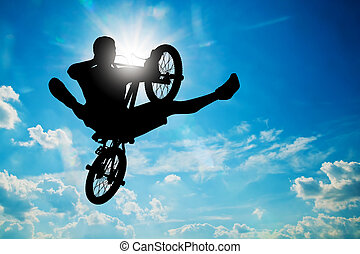 Man jumping on bmx bike performing a trick against sunny...