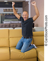 Man jumping on couch in shop