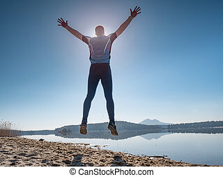 Man jumping on the beach at sunset. Funny happy man