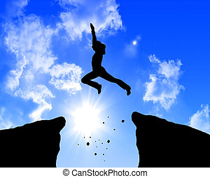 man jumping on the rocks against blue skymountain